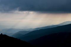 层状山坡和云彩在蓝色树荫下 库存图片