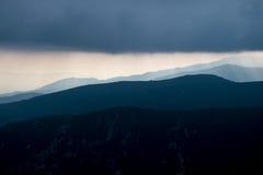 层状山坡和云彩在蓝色树荫下 免版税图库摄影