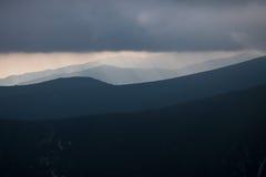 层状山坡和云彩在蓝色树荫下 库存照片