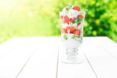 层状点心用在木桌上的草莓和乳脂干酪在绿色庭院背景 免版税库存图片