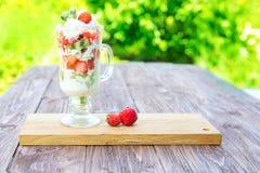 层状点心用在木桌上的草莓和乳脂干酪在绿色庭院背景 库存图片