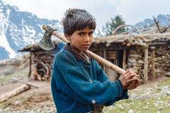 居住在喜马拉雅山的男孩拿着轴 免版税库存照片