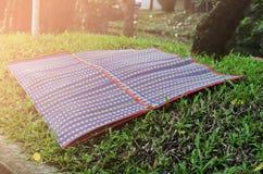 居住在庭院的传统泰国席子与阳光backgrou 库存图片