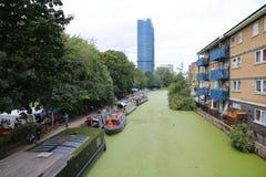 居住船和狭窄的小船行在运河银行 免版税库存图片