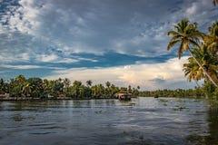居住船在有天空和棕榈树的死水 免版税库存图片