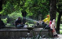 居民在公园放松在雕象Partini Balaikambang下 免版税图库摄影