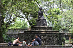 居民在公园放松在雕象Partini Balaikambang下 库存图片