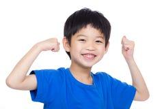 屈曲二头肌的亚洲小男孩 免版税库存图片