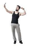 屈曲二头肌胳膊肌肉的适合的年轻人,当拍与手机时的selfie照片 库存照片