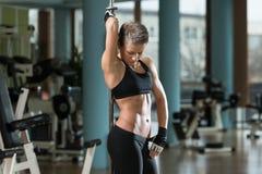 屈曲在一家健康俱乐部的健身妇女肌肉 免版税库存照片