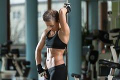 屈曲在一家健康俱乐部的健身妇女肌肉 库存图片