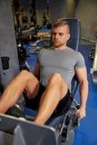 屈曲在健身房机器的人腿肌肉 库存图片