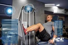 屈曲在健身房机器的人腿肌肉 免版税库存照片