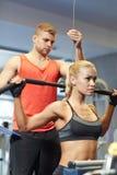 屈曲在健身房机器的男人和妇女肌肉 库存照片
