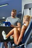 屈曲在健身房机器的男人和妇女肌肉 免版税图库摄影