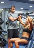 屈曲在健身房机器的男人和妇女肌肉 免版税库存照片