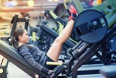 屈曲在腿新闻机器的妇女肌肉在健身房 库存照片