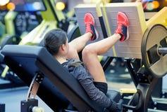 屈曲在腿新闻机器的妇女肌肉在健身房 库存图片