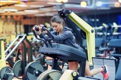屈曲在腿新闻机器的妇女肌肉在健身房 免版税库存照片