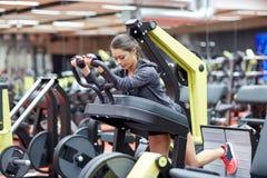 屈曲在腿新闻机器的妇女肌肉在健身房 图库摄影
