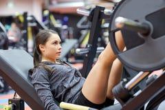 屈曲在腿新闻机器的妇女肌肉在健身房 免版税图库摄影