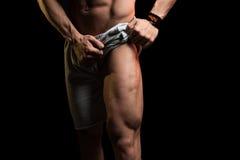 屈曲在黑背景的肌肉人腿肌肉 库存图片