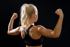 从屈曲她的二头肌的后面的运动的妇女 免版税库存图片