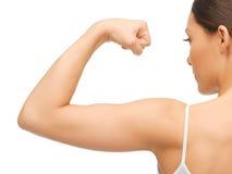 屈曲她的二头肌的运动的妇女 免版税库存照片