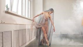 屈曲她的腿的飞行的礼服的芭蕾舞女演员准备对在阶段的表现 股票录像