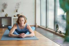 屈曲她的身体的纯熟女性信奉瑜伽者 库存图片