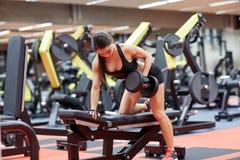 屈曲有哑铃的少妇肌肉在健身房 图库摄影