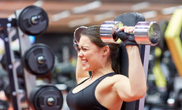 屈曲有哑铃的少妇肌肉在健身房 免版税库存照片