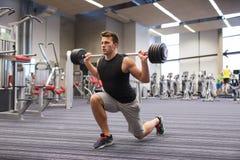 屈曲有杠铃的年轻人肌肉在健身房 免版税库存图片