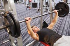 屈曲有杠铃的年轻人肌肉在健身房 免版税库存照片