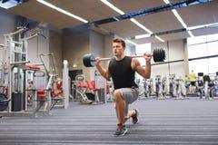 屈曲有杠铃的年轻人肌肉在健身房 库存图片