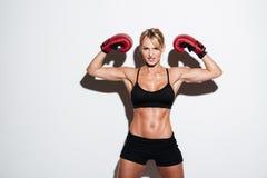 屈曲肌肉的一名年轻运动员妇女的画象 免版税库存图片