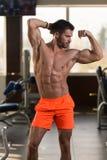 屈曲肌肉的健康年轻人 免版税库存图片