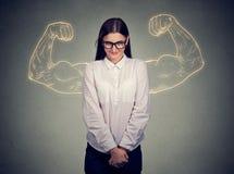 屈曲肌肉的强有力的害羞的讨厌的女孩 免版税库存图片