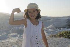 屈曲肌肉的愉快的女孩 免版税库存图片
