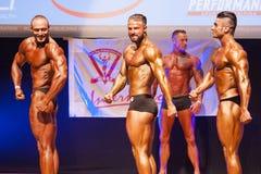 屈曲肌肉的男性爱好健美者在阶段的冠军 免版税库存图片