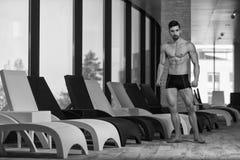 屈曲肌肉的年轻人在太阳懒人 免版税库存照片