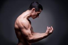 屈曲肌肉的年轻爱好健美者 库存图片