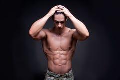 屈曲肌肉的年轻爱好健美者 免版税库存图片