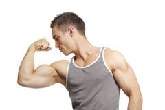 屈曲胳膊的肌肉年轻人在体育运动成套装备干涉 库存照片
