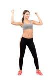 屈曲胳膊肌肉的年轻激动的健身妇女 库存图片