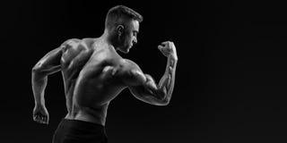 屈曲他的胳膊的一个运动肌肉人的强的后面 库存照片