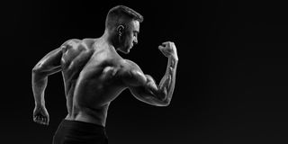 屈曲他的胳膊的一个运动肌肉人的强的后面 库存图片