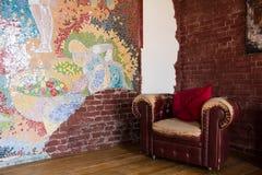 屋子的内部有一把老皮革扶手椅子和砖墙的 库存图片