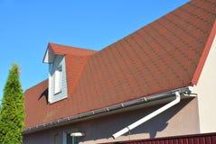 屋顶与青苔的沥青木瓦 雨与水落管管子和顶楼有双重斜坡屋顶的房屋窗口的天沟管道 图库摄影