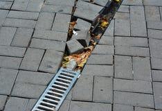 屋顶决赛的残破的雨天沟水落管管子与在路面的损坏的开阔水域排水设备对修理 免版税库存图片